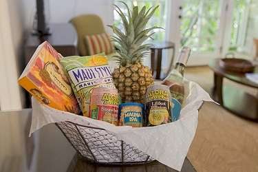 Gift basket with a bottle of wine, pinapple, juice, macadamia nuts, and Hawaiian chocolates offered by Coconut Condos Vacation Rentals.
