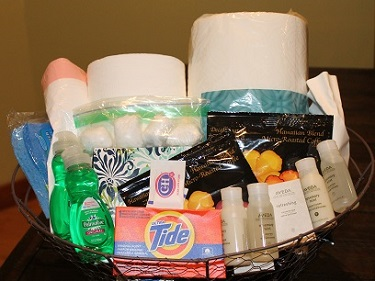Coconut Condos Amenity Basket with laundry detergent, shampoo, toilet paper, paper towel, and more.