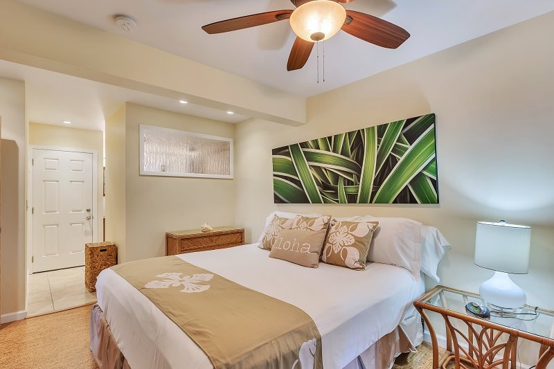 Luxury bedding with Hawaiian design pillows on a queen size bed inside a Maui vacation rental condo